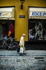 Kramarska street (ewitsoe) Tags: street woman poland poznan canon eos5ds 50mm yellow lady older elder cobblestones summer erikwitsoe ewitsoe urban cityscape day dress light shadows window bike quiet