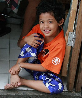 curly haired boy sitting on a tile floor