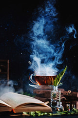 Hot steaming tea with an open book (Dina Belenko) Tags: food drink steam vapour dark contrast magic tea hot beverage book leisure reading weekend cozy rest home concept cup alchemy glass background herbal healthy black chemistry fantasy flowers liquid smoke spell teacup table leaves wizard aroma breakfast evening natural red view autumn cold nature weather composition lifestyle relaxation stilllife