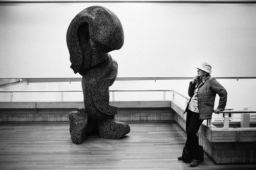 woman next to a huge pile of art