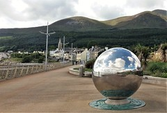 Weather in a mirror ball, Newcastle, Co. Down ... below the Mourne Mountains (ronmcbride66) Tags: weather mournes newcastle countydown mirrorball mirror promenade streetfurniture streetart urban seasideresort church forest skyline clouds allroundvision globe sphere