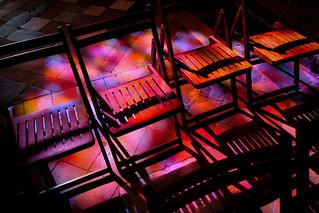 Sonnenlicht fällt durch ein buntes Kirchenfenster auf Stühle in der Klosterkirche von Corbara in Korsika