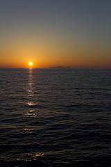 Descent into darkness (Lens_Flaire) Tags: ocean sea sunset darkness reflection ripple wave alone horizon island distant distance orange sky clear water greece santorini oia ammoudi