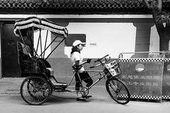 No one for a tour (Go-tea 郭天) Tags: beijing hutong gulou bike bicycle ride transportation transport business duty job alone lonely no clients customers old ancien traditional tradition power spirit time history historical historic guide waiting wait boring bored candid portrait cap hot warm woman lady cloves basket street urban city outside outdoor people bw bnw black white blackwhite blackandwhite monochrome naturallight natural light asia asian china chinese canon eos 100d 24mm prime
