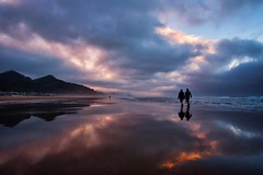 Strolling through sunset (Jim Nix / Nomadic Pursuits) Tags: jimnix nomadicpursuits travel oregon cannonbeach beach coastline coast pacificocean pacificnorthwest pacnw sunset golden hour dramatic beautiful sandy ocean wet reflection reflections clouds colorful couple walking strolling sony sonya7ii 1635mm sonyimages