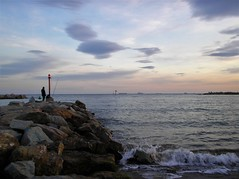 A thinking fisherman on the rocks (Francesco Pesciarelli) Tags: flickr pesha sky clouds waves sea mediterraneo water colors fisherman silhouette rocks life big downloadable mentionmyname varied collection thoughtful colours
