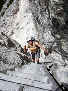 Edita ascends a wooden ladder on Monte Piana