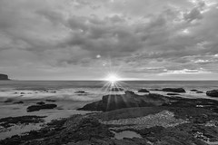 Cloudy Sunrise Seascape (Merrillie) Tags: daybreak sand landscape nature water newsouthwales rocks sun nsw sunburst beach scenery monochrome starburst australia clouds newport earlymornings waterscape sea blackandwhite dawn seascape