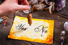 Pendulum, tool for dowsing in hand, over yes and no choosing diagram (Psychic Base) Tags: advise advisor choosing chose decision divination dowse dowser dowsing esoteric forecast foresight fortune fortunetelling future hand hesitate hypnosis hypnotic hypnotising hypnotist magical making measurement measuring metaphysical mystery mystic mystical mysticism no pendulum predict prediction prophecy psychic radiesthesia radionics signs spirit spiritual suggest swinging teller time traditional wood wooden yes