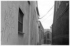Here Again... (h_cowell) Tags: alley alleyway walls texture brick graffiti street light dark shadow atmosphere streetphotography grain grainy film filmisnotdead filmphotography believeinfilm praktica 135 analogue macclesfield appicoftheweek hp5