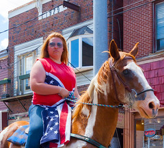 Flags In Her Eyes  *Explore* (John Kocijanski) Tags: red people glasses flags horse animal woman candid streetphotography streetcandid portrait parade canon24105mmf4l canon5dmkii
