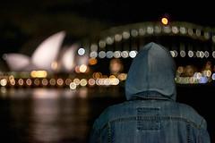 Boy in the hood (rvrossel) Tags: sydney operahouse sails harbourbridge coathanger harbour lights night nightlights reflection water colour man boy hood fujixt10 helios44m58mmf2 helios bokeh fujixseries fujishooters fujilove