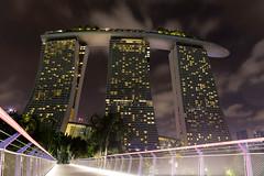 Froschperspektive. Das Hotel Marina Bay Sands bei Nacht (wuestenigel) Tags: digitalnomad reise singapur reisen singapore asia travel reiseblogger city stadt architecture diearchitektur building gebäude urban städtisch business geschäft downtown innenstadt blur verwischen sky himmel noperson keineperson light licht outdoors drausen skyscraper wolkenkratzer cityscape stadtbild street strase bridge brücke high hoch evening abend dusk dämmerung water wasser