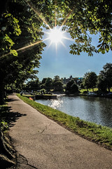 sunny day (I was blind now I see!) Tags: sun sunny flare sunspot reflection tree trees framed sunstars treeline canal river water sky blue green path