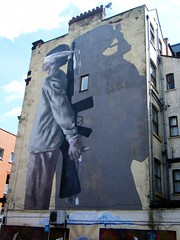 Manchester street art - blindfolded man with machine gun over shoulder, with his hands tied behind his back (rossendale2016) Tags: wall ofhim silhouette shadow gun machine blindfolded back his behind tied hands handcuffed man large end gable art street manchester