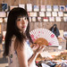 Young woman shopping in traditional Japanese retail store, holding paper fan