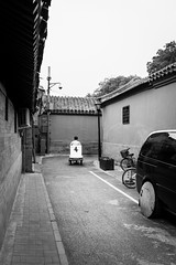 To be delivered (Go-tea 郭天) Tags: beijing hutong gulou motorbike motorcycle electric power ride riding man busy work working duty business alone lonely quite old traditional tradition historic historical history narrow alley ancient building construction house car candid back backside movement leaving curve transportation transport through street urban city outside outdoor people bw bnw black white blackwhite blackandwhite monochrome naturallight natural light asia asian china chinese canon eos 100d 24mm prime bikes bicyles