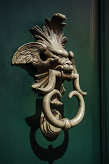 Serious2 (Мaistora) Tags: door knocker bronze detail fragment cast casting brass alloy gold mythical creature green metal relief structure texture shape art sculpture design classic medieval historic antique old typical light shadow angle eyes angry serious menacing wings winged head walkby passingby street city urban centre milan milano lombardia lombardy italy italia sony ilce alpha a6000 sel1650pz lightroom