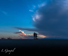 Couple photographing a dramatic sunset (Lgampel) Tags: blue silhouettes sunset sky florida clouds outdoors beautiful couple panorama view bikes evening sun gravel man women young sunlight outdoor summer background nature dramatic everglades rivergrass