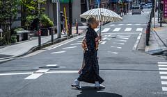 2017 - Japan - Yokohama - Crossing (Ted's photos - For Me & You) Tags: 2017 cropped japan nikon nikond750 nikonfx tedmcgrath tedsphotos vignetting yokohama umbrella streetscene street crosswalk bollards sidewalk female vehicles shadow shadows bicycle walking people peopleandpaths red redrule