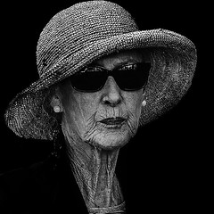 Portrait (D80_482684) (Itzick) Tags: denmark copenhagen candid bw blackbackground bwportrait streetphotography shades earrings elderlywoman portrait face hat d800 itzick