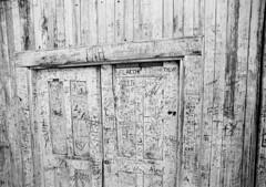 (nico.padayhag) Tags: 35mm blackandwhite bw kodak nikon writing wood door building old decaying abandoned decay carved names haunted town village bayarea locke frame contrast