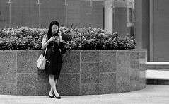 Lunch Date Wait (burnt dirt) Tags: houston texas downtown city town street sidewalk crosswalk girl woman man couple crowd grouppeople person asian latina blonde brunette cute sexy laugh smile jeans dress skirt shorts yogapants tights leggings longhair shorthair ponytail heels stilettos boots shadow sunny reflection stockings friend lover pregnant athlete exercise glasses sunglasses phone cellphone construction traffic office building worker lunch streetphotography documentary portrait fujifilm xt1 bw blackandwhite tattoo metro bus busstop trainstop