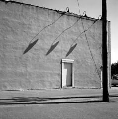 3-lamps (kaumpphoto) Tags: bw saintpaul lamps shadow rolleiflex tlr street asphalt pole door three bricks alley light lighting 120
