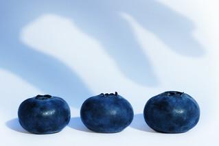 1 robber's hand. 3 blueberries in danger.
