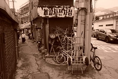 """Seoul Korea Hongje-dong retro bike alley in monochrome - """"Ridden Hard and Put Away..."""" (moreska) Tags: seoul korea hongjedong backalley rusty crusty battered clutter junk mess urban unstaged street alleyway narrow sign hangul fade blackandwhite sepia monochrome outdoor bicycle frame pushcart gritty neighborhood oldschool disappearing 홍제동 gangbuk capital rok asia"""