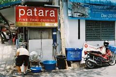Fine Thai Cuisine (35mm) (jcbkk1956) Tags: gold200 thai man motorcycle bike signs restaurant street kodakgold200 kodak olympustrip olympus analog film 35mm thonglo thailand bangkok worldtrekker