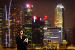 Pretty office lady is using smart phone in financial district area in cityscape at night (Krunja) Tags: 3034years adultsonly buildingexterior chinaeastasia chineseethnicity citylife colorimage digitaltablet focusonforeground lookingdown midadult onemidadultwomanonly oneperson onewomanonly onlywomen sideview waistup adult city coat connection financialdistrict holding horizontal illuminated network night outdoors panoramic people photography singapore skyscraper standing technology wifi sg