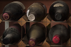 Wine rack: a bit of order (andypf01) Tags: flickrfriday abitoforder wine bottles winerack storage dust cobwebs atmosphere dirt colour fujixt2 samyang100mmf28lens