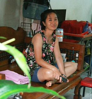 a pretty woman with a remote and teak furniture