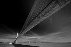 "fine art black & white perspective of Pont du Normandie chasing its shadow across the Seine River, near Honfleur, Normandy, France (grumpybaldprof) Tags: noiretblanc ""blackandwhite"" ""blackwhite"" monochrome bwfineart ""fineart"" impressionist impressionistic ethereal artistic shadow light contrast texture tone blacksky honfleur normandy normandie france calvados ""pontdenormandie"" bridge amazing huge impressive ""longestuntil2004"" ""bridgeofnormandy""""cablestayed"" ""cablestayedroadbridge"" ""lehavre"" ""seine ""riverseine"" ""laseine"" ""michelvirlogeux"" ""normanfoster"" river piers cables road traffic sky ocean altantic rock concrete patters lines angles boat canon 70d ""canon70d"" sigma 1020 1020mm f456 ""sigma1020mmf456dchsm"""