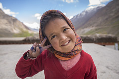 Peace [Explored] (Ravikanth K) Tags: beautiful shy kid child girl red uniform school pin valley spiti himachal pradesh india mountains hills teeth peace happy innocent outdoor break highaltitude clouds pleasant