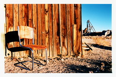 Take A Seat (tobysx70) Tags: nikon f2 photomic kodak ektachrome lumiere 100 professional 35mm 135 color slide film 5046 lpp crossprocessed xpro rollfilmweek july 2017 take a seat gold point nevada nv abandoned chrome chair shadow wooden cabin building silver mine mining ghost town blue sky day1 toby hancock photography
