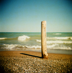 doesn't matter (.grux.) Tags: holga120n film lomography colourslide200 120 mediumformat 6x6 xpro crossprocessed plasticfantastic zonefocus beach shore sand rocks water waves time sundial log accurate thepinery lakehuron