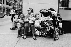 Gathering at the Corner (stillsguy) Tags: nyc summer bw caretaker kids baby carriage handsfull midtown preoccupied restless waiting hoping future pedestrians shop window reflection unawares streetphotography olympus om3ti zuiko 40mm f2 kodak tmax 3200 film