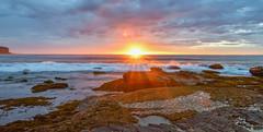 Cloudy Sunrise Seascape with Sunburst (Merrillie) Tags: daybreak sand landscape nature water newsouthwales rocks nsw beach scenery sunburst sun clouds newport earlymornings waterscape sea australia dawn seascape