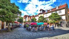 Pavement cafe @ Lindau, Germany [2017] ([ PsycBob ]) Tags: strasencafe pavement cafe lindau bodensee lake constance blue sky blauer himmel wolken clouds sonnnschirme sunshade