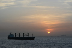IT IS SUNSET IN PORT OF  DAKAR,  SENAGAL.  MARINE CLOUD COMING IN.      (FISHERMEN IN THEIR WOODEN BOATS, AND A CONTAINER SHIP. ) (vermillion$baby) Tags: atlantic boat color dakar harbour ocean port sea senagal ship silhouette son sunset vessel coasr sunrise senegal bow water travel world international orange coast cloud