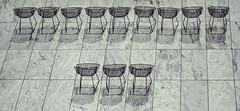 """Panoramic View Of One Dozen Metal Seats at MoMA's Sculpture Garden Waiting For A Patron"" - taken on July 20, 2017 (nrhodesphotos(the_eye_of_the_moment)) Tags: dsc65933001024 ""theeyeofthemoment21gmailcom"" ""wwwflickrcomphotostheeyeofthemoment"" summer2017 season outdoors moma reflections shadows panoramic outdoor metal marble tiles panoramicviewofonedozenmetalseatsatsculpturegardenwaitingforapatron"