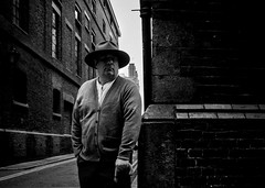 The man in the Fedora Hat (markfly1) Tags: street candid black white monochrome bw mono fedora hat man walking umbrella corner junction eye contact leading lines brickwork streetlife people england uk