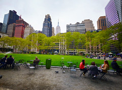 Park in New York City (` Toshio ') Tags: toshio newyorkcity nyc newyork bryantpark midtown manhattan park people architecture city trees grass buildings america usa fujixe2 xe2 empirestatebuilding