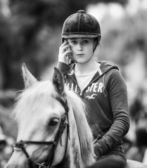 A modern Miss .... Riding while on the phone (Frank Fullard) Tags: frankfullard fullard riding jockey horse mobile phone telephone dangerous modern candid street portrait stupid horsefair fair irish ireland