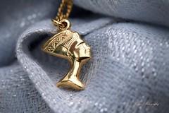 Golden queen... (Maria Godfrida) Tags: macro macromondays queen nefertiti beauty gold charm pendant closeup tamron nikon necklace bokeh blue dof golden jewellery hmm mm 7dwf