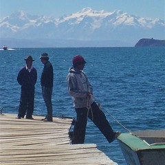Bolivian man tying up the boat in #LakeTiticaca with beautiful #SnowCappedMountains in the background. This enchanting #island is one of #Bolivia's #TreasuresOfTraveling in #SouthAmerica! Find out more about Isla del Sol here: http:// treasures4oftravelin (TreasuresOfTraveling) Tags: island snowcappedmountains southamerica bolivia treasuresoftraveling laketiticaca
