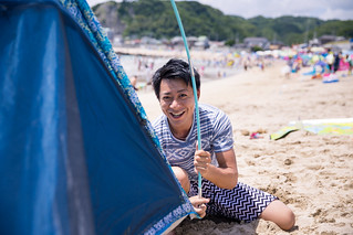 Young man setting up tent on beach