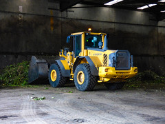 A Yellow Volvo (Steve Taylor (Photography)) Tags: volvo tractor building yellow green brown newzealand nz southisland canterbury christchurch plant leaves branch bromley centre compost composter greenwaste recycle yard digger